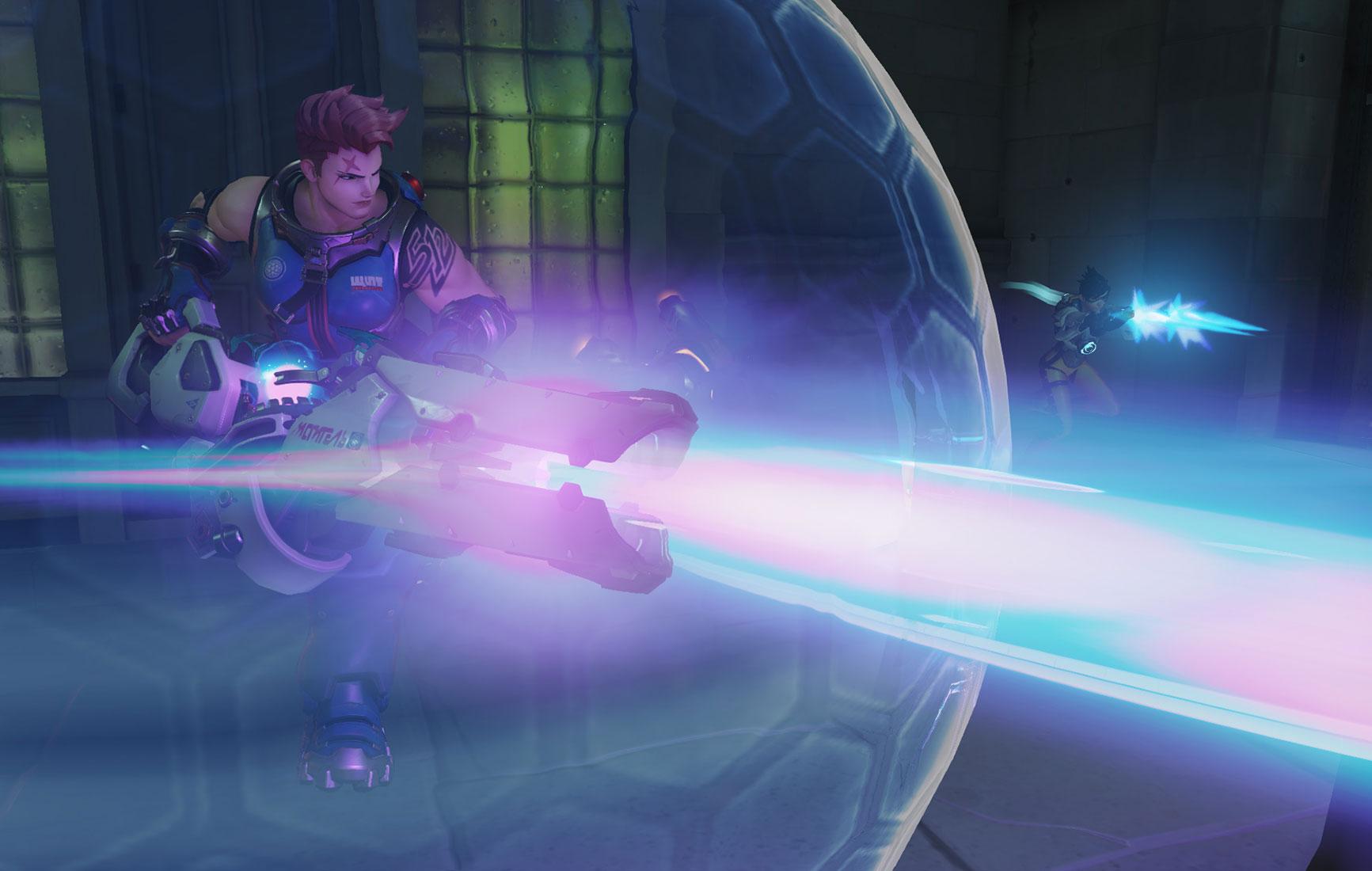Videopelikuvaa Overwatch-pelistä. Kuvassa etualalla Zarya-hahmo, isokokoinen ja lihaksikas, pinkkitukkainen nainen. Hän ampuu protonisädettä valtavasta aseestaan, ja hänen ympärillään on suojakupla. Taustalla pienikokoinen ja vikkelä Tracer-hahmo ampuu nopeilla automaattipistooleillaan.